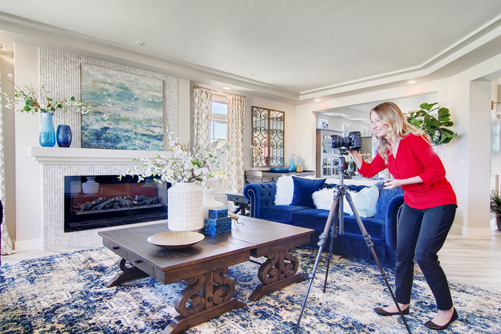 real estate photographer in living room with tripod wearing a red shirt.