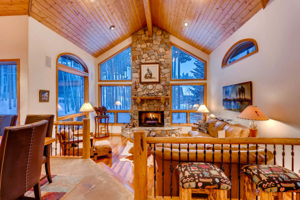 A mountain home living room with large windows. Fireplace with fire blazing. Real Estate listing image.